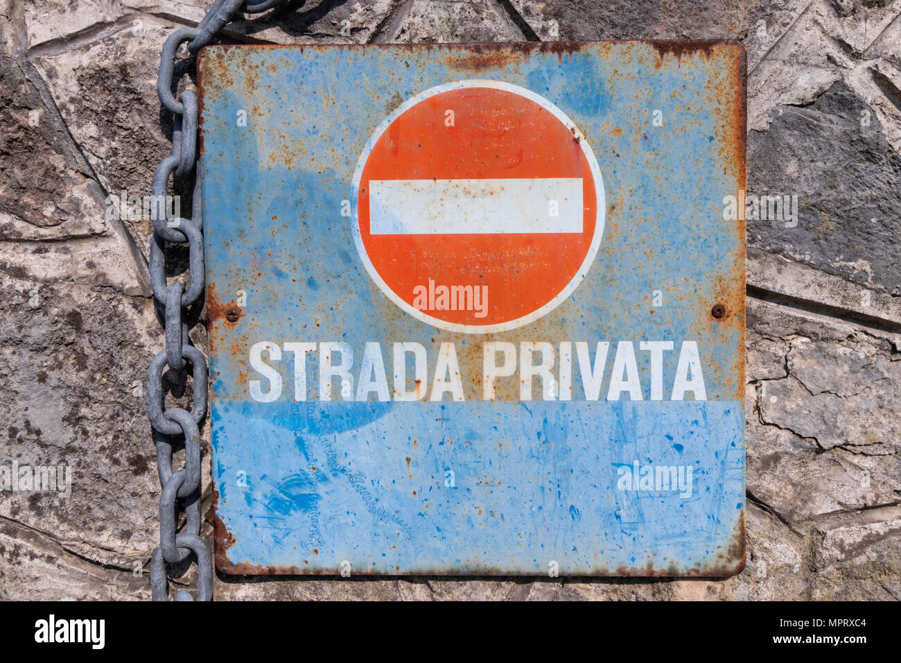 Rusty italian no entry signpost with private road indication fixed on a stone wall and a chain Stock Photo