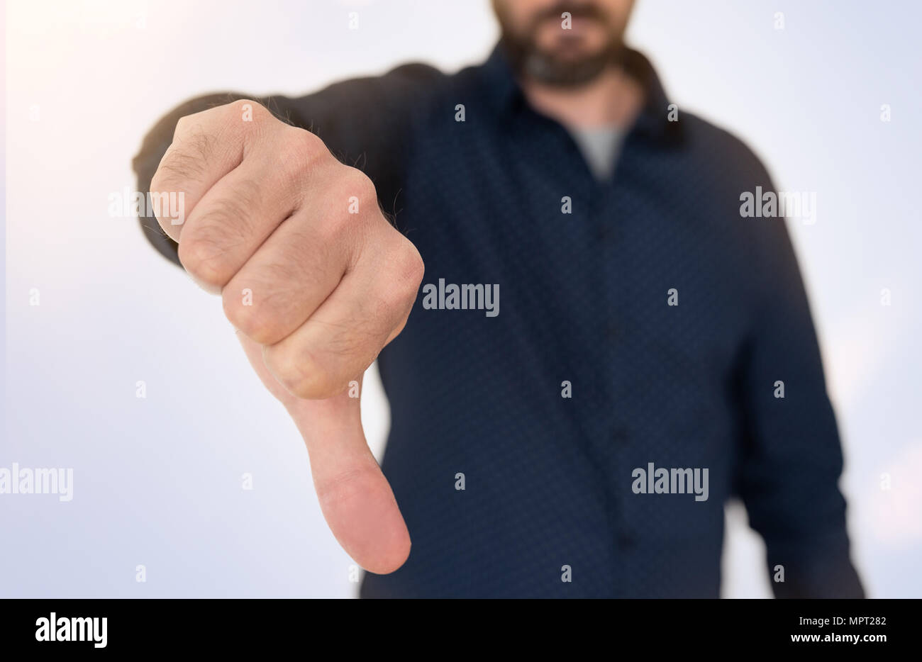 businessman in blue shirt showing thumbs down gesture - Stock Image