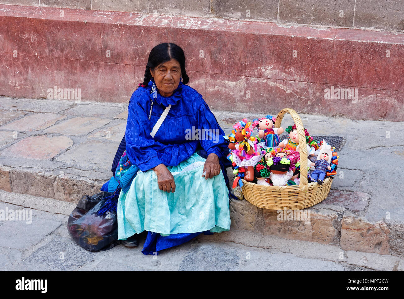 Otomi indian woman sells handmade folk art dolls in San Miguel de Allende, Mexico. Otomi are the oldest largest indigenous group inhabiting the region. - Stock Image