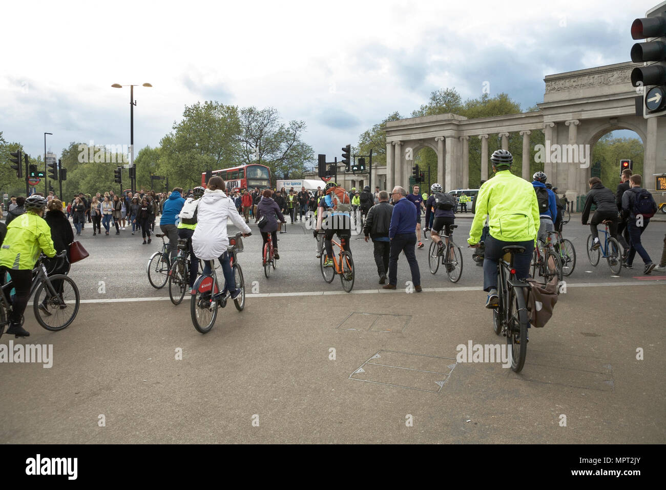 Hyde Park Corner London cyclists and pedestrians crossing a road. Commuting by bike in London. - Stock Image