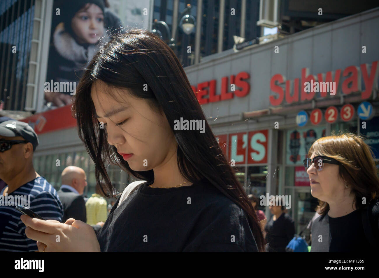 A distracted millennial, engrossed in her smartphone, in New York on Monday, May 21, 2018.  (© Richard B. Levine) - Stock Image