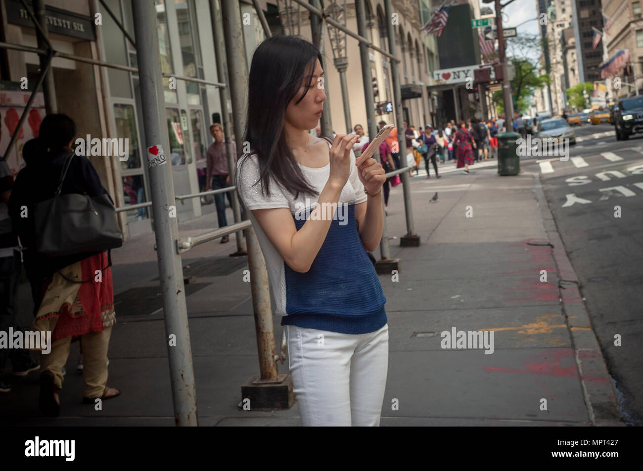 A distracted millennial, engrossed in her smartphone, waits for a bus on Fifth Avenue in New York on Sunday, May 20, 2018.  (© Richard B. Levine) - Stock Image