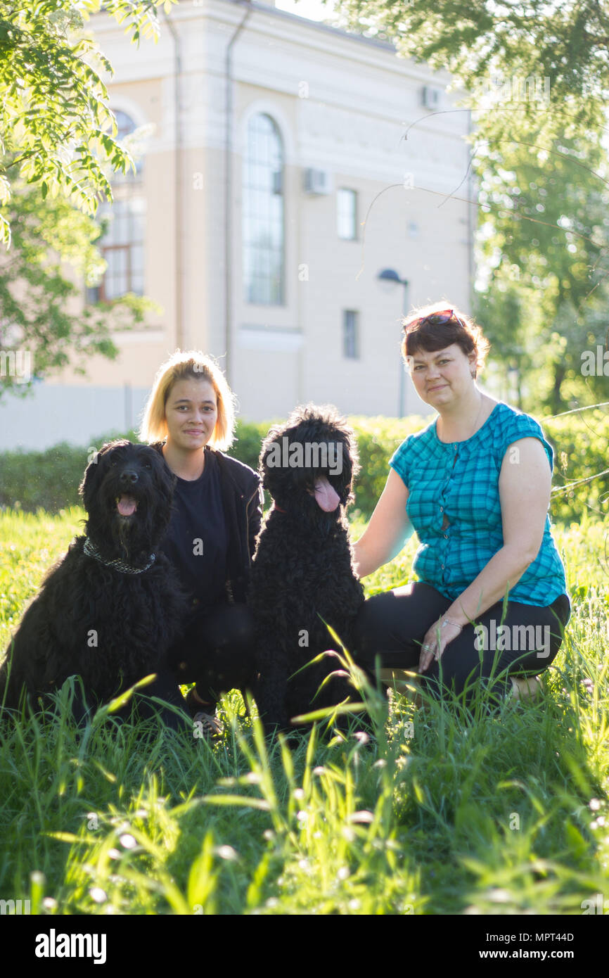 The girl and her mother and two black Russian Terrier sitting on the grass in the Park - Stock Image