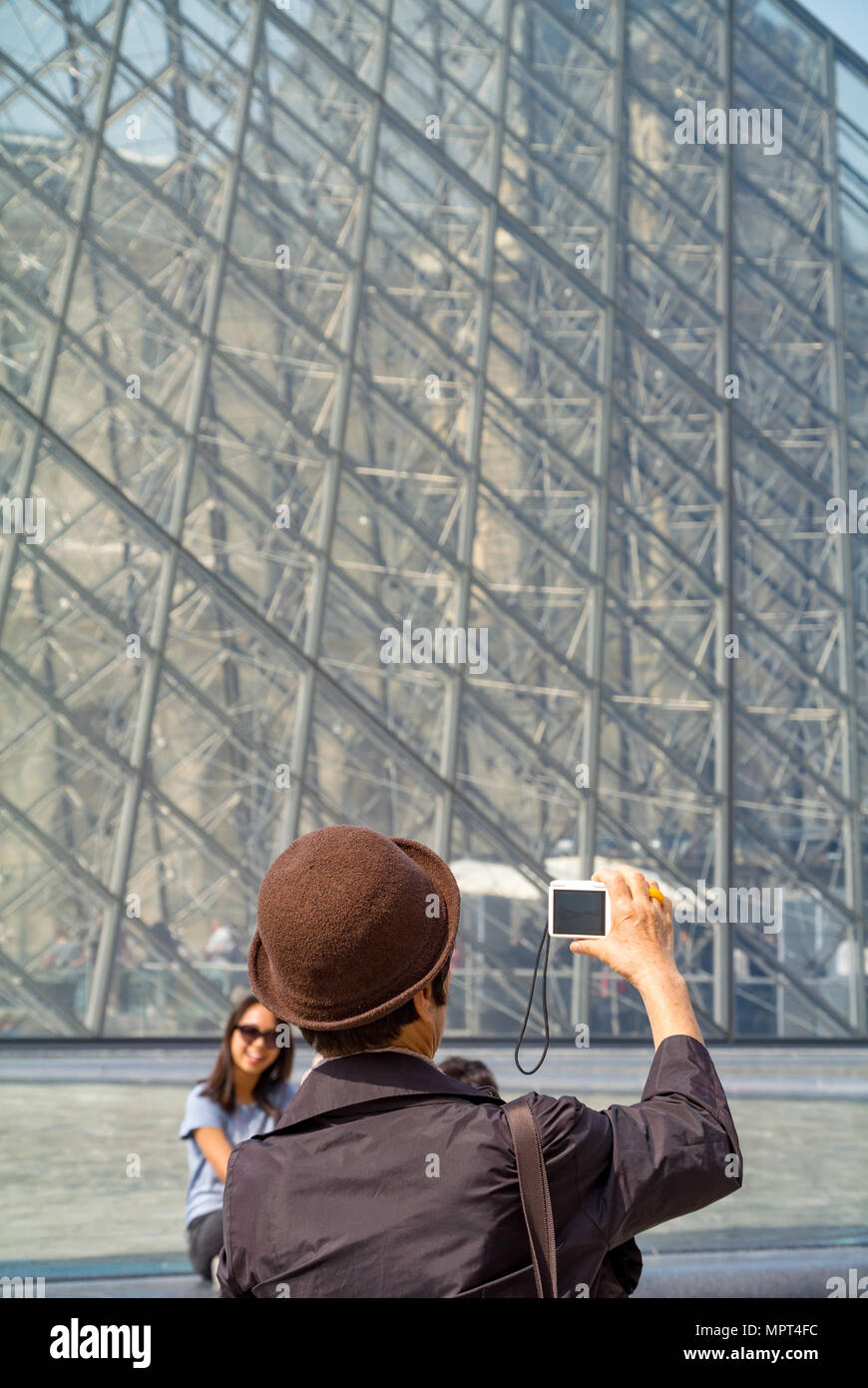 An Asian female tourist taking a photo at pyramid of Louvre Museum, Paris, France - Stock Image