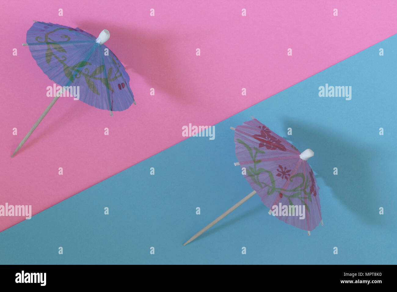 Creative view of a cocktail umbrella on a two-tone background - pink and blue. Conceptual image of summer. Minimalism.  Summertime. Top view. - Stock Image