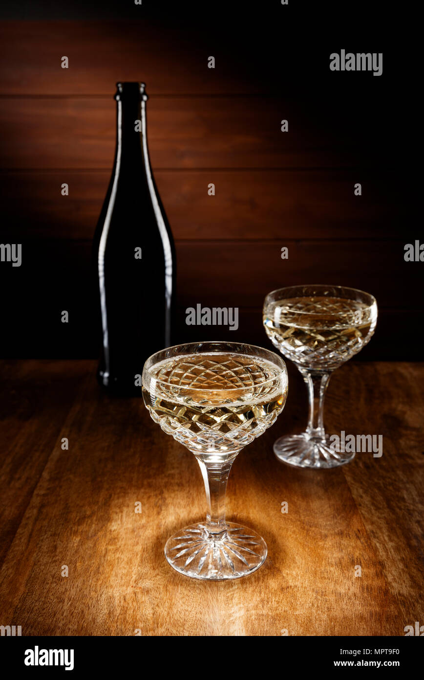 Spotlight on two Champagne crystal glasses with a bottle in background, shot on a antique wooden table top. - Stock Image
