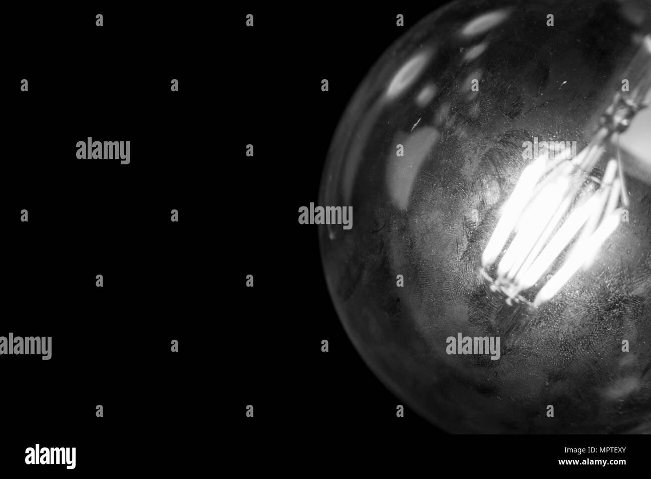 A vintage style glowing lightbulb, illuminate the dark room. - Stock Image