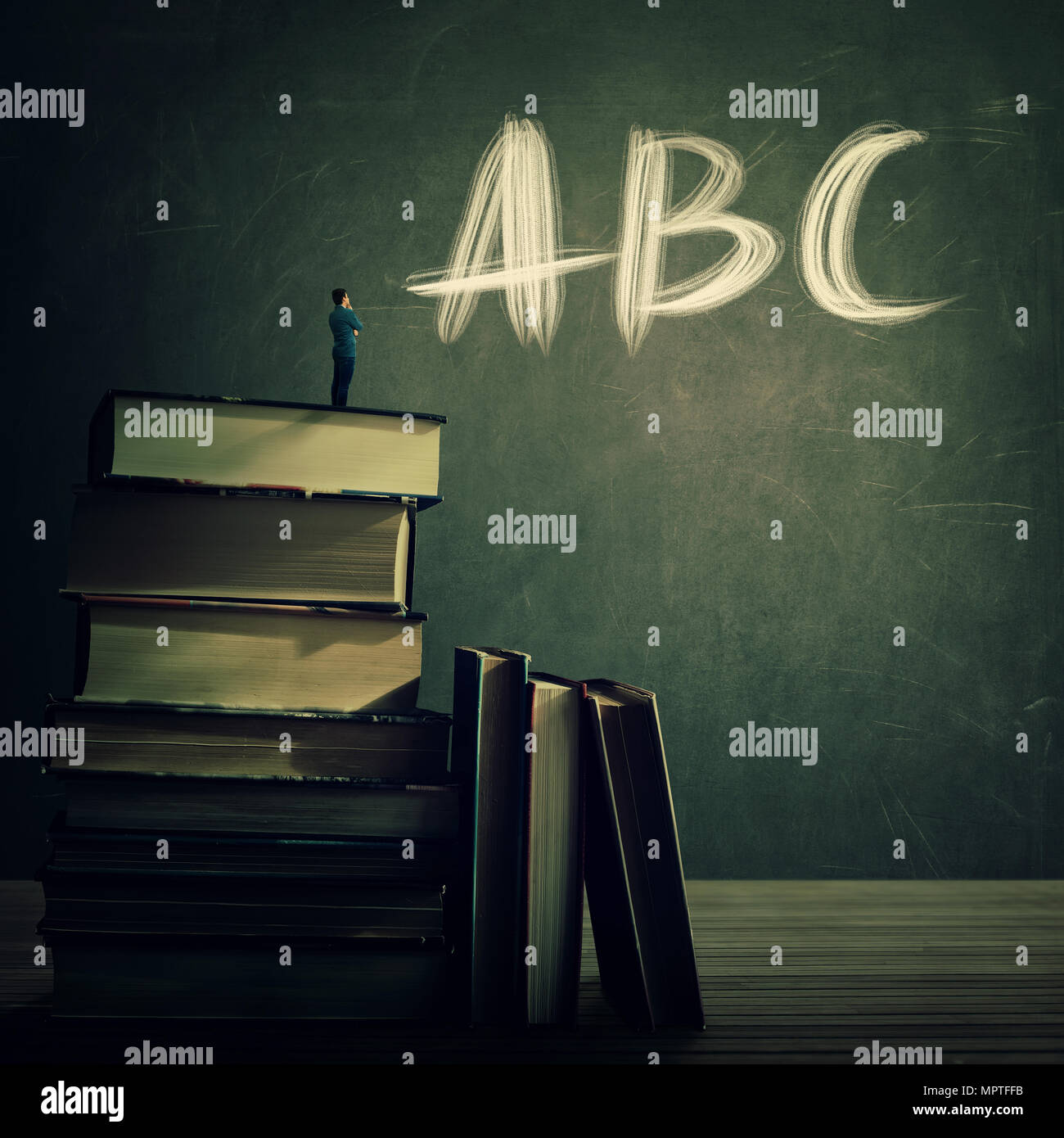 Teacher stand on the top of a huge books pile looking at the blackboard with ABC letters written. Education and knowledge concept. Teaching practice f - Stock Image