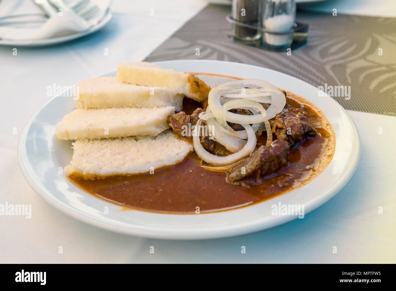 Czech beef goulash with knodel on a white plate. Goulash with bread dumplings. - Stock Image