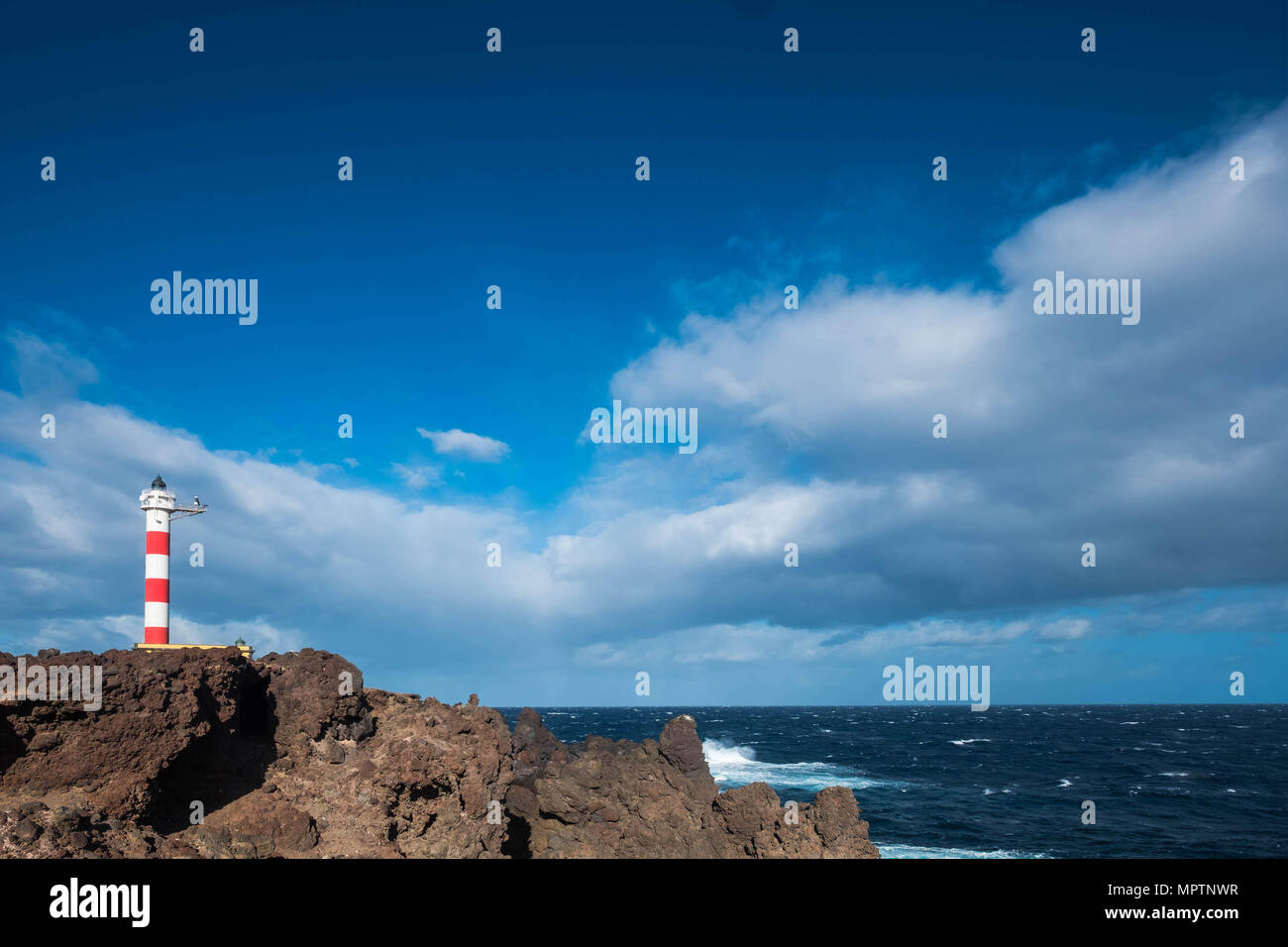 old style classic lighhouse on the coast of Tenerife in the middle of the atlantic ocean. Power of the wave and isolated home. Beautiful blue sky. Fre - Stock Image