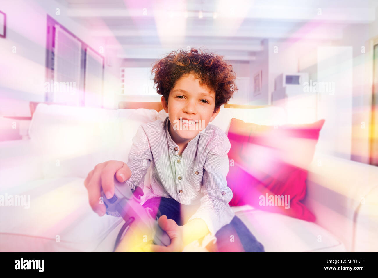 Portrait of preteen boy smiling and playing video games - Stock Image