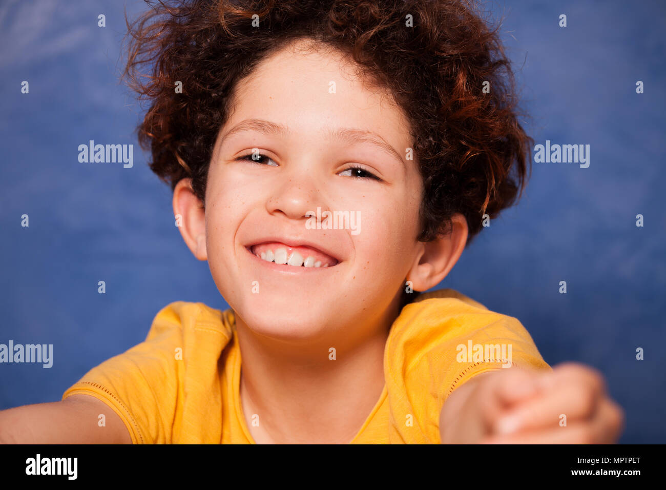 Close-up portrait of preteen curly boy smiling and looking at camera - Stock Image