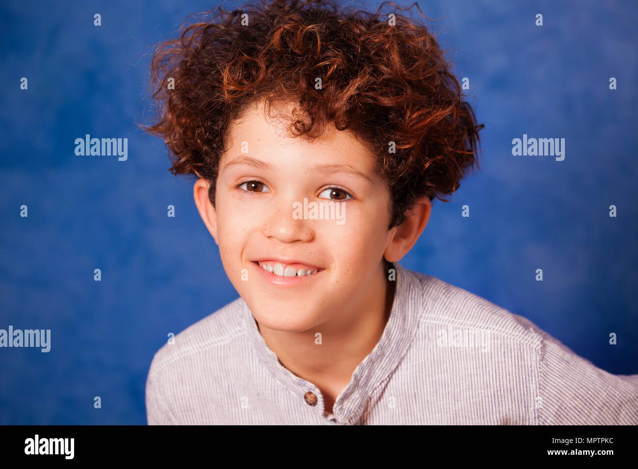 Close-up portrait of smiling preteen boy with curly hair and brown eyes against blue background - Stock Image