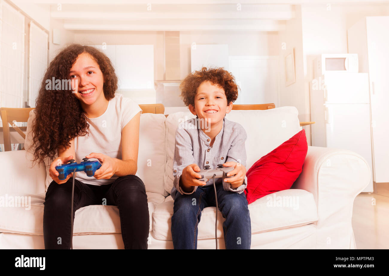 Portrait of happy children, teenage girl and preteen boy, sitting on the sofa, playing video games - Stock Image