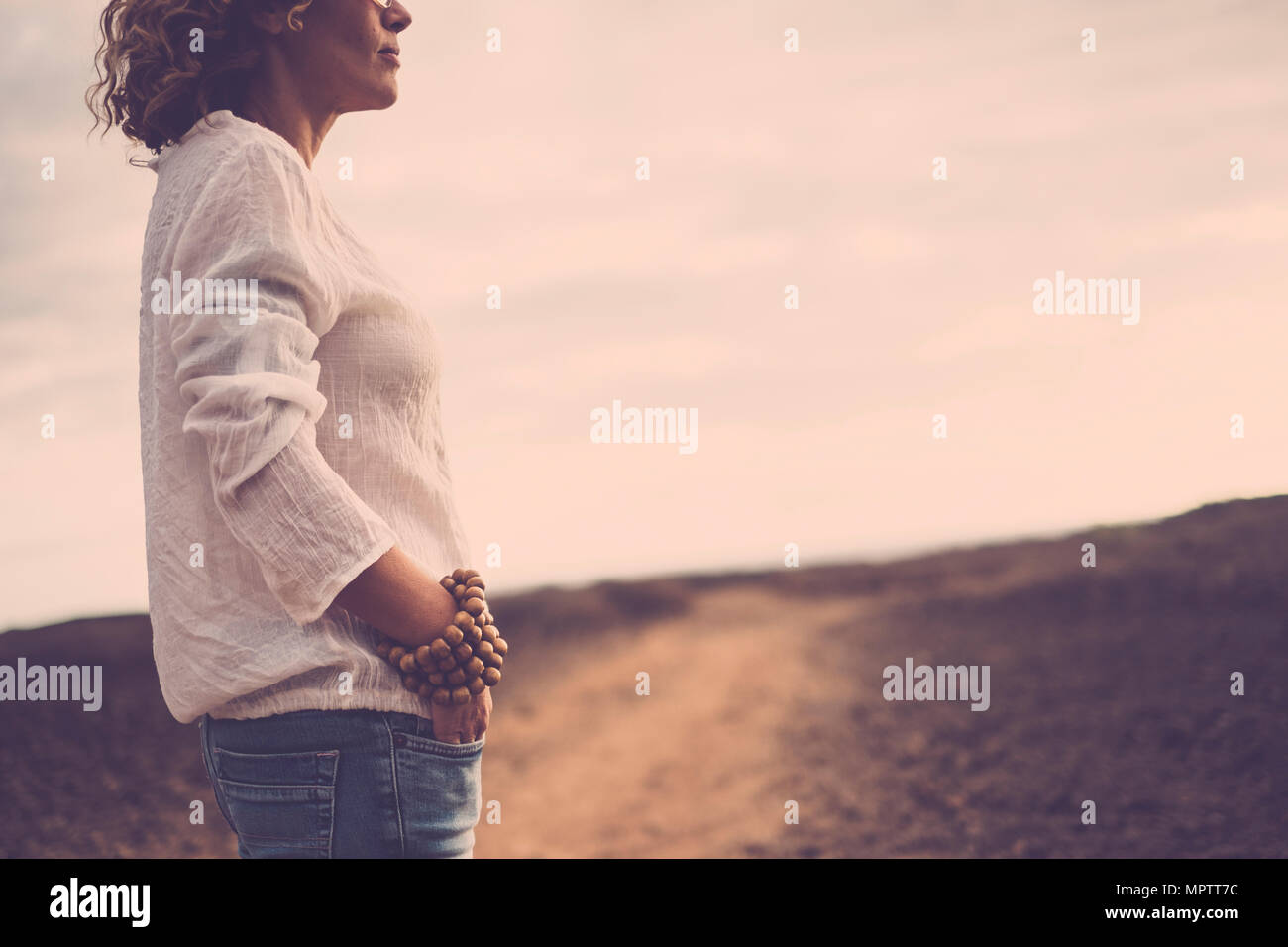 beautiful middle age caucasian woman stand up near the desert - Stock Image