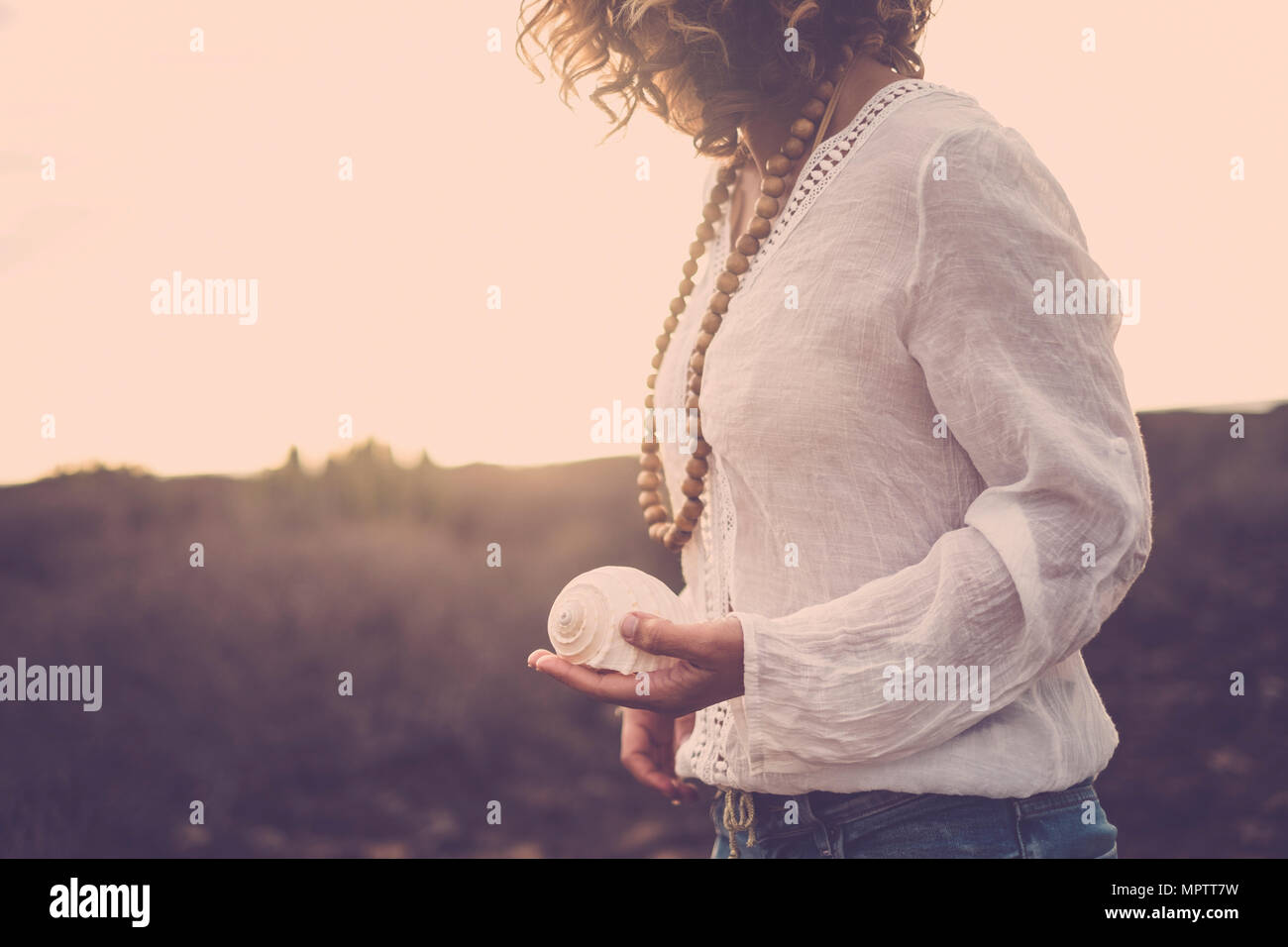 nice cut for beautiful middle age 40 years old model lady immersed in the nature of a desert. she take a shell on her hand for nature connection conce Stock Photo