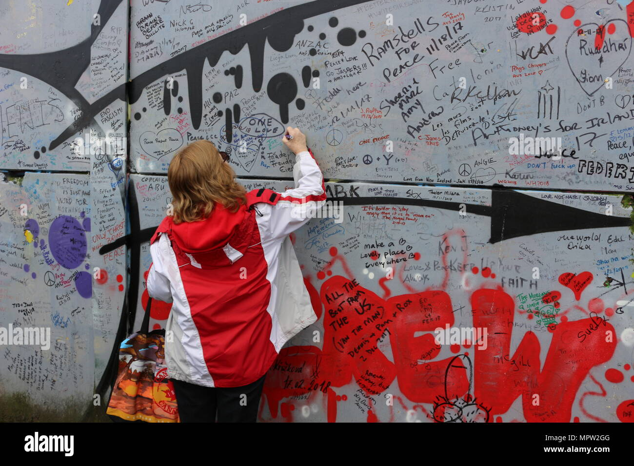 Tourist writes on the peace wall in Belfast that signifies the political peace that now occurs. - Stock Image
