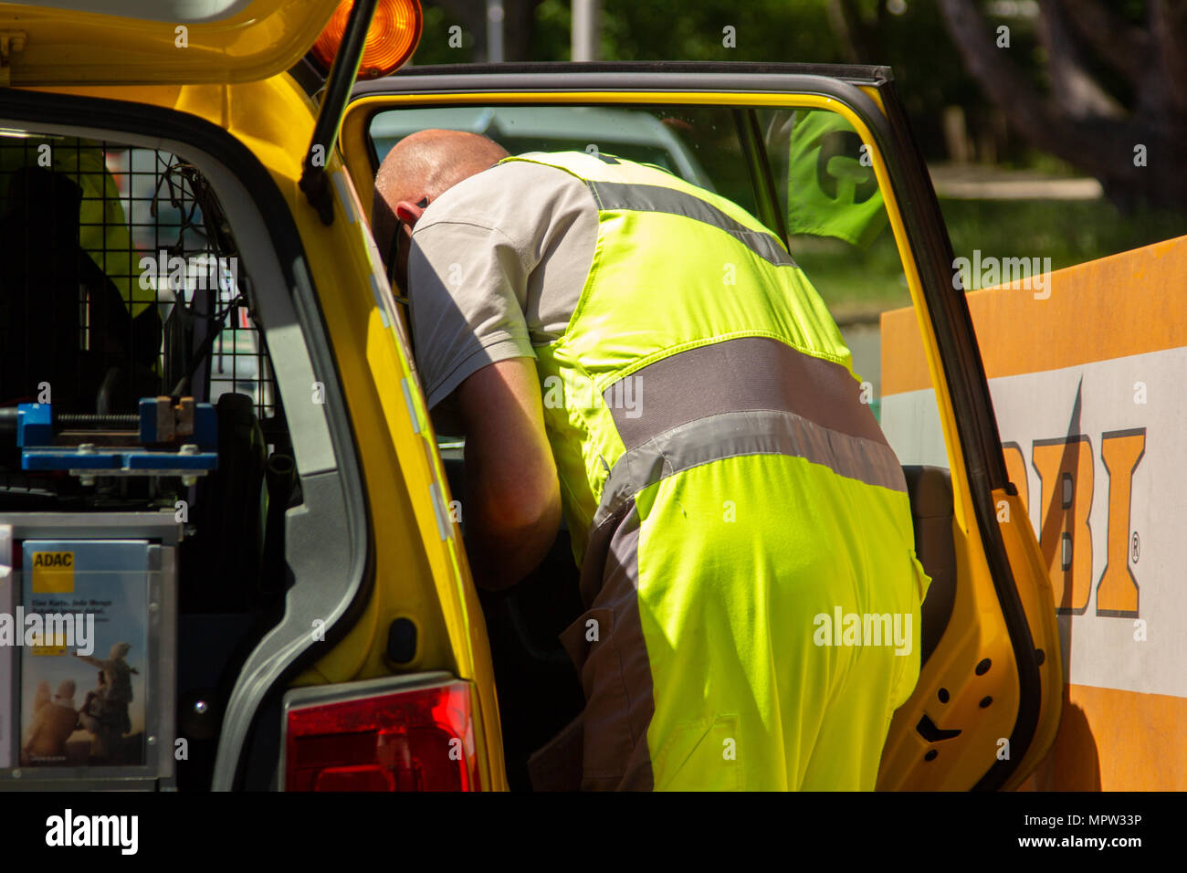 HANNOVER / GERMANY - MAY 21, 2018: Service man from ADAC, german automobile club stands at the trunk of his service car. - Stock Image