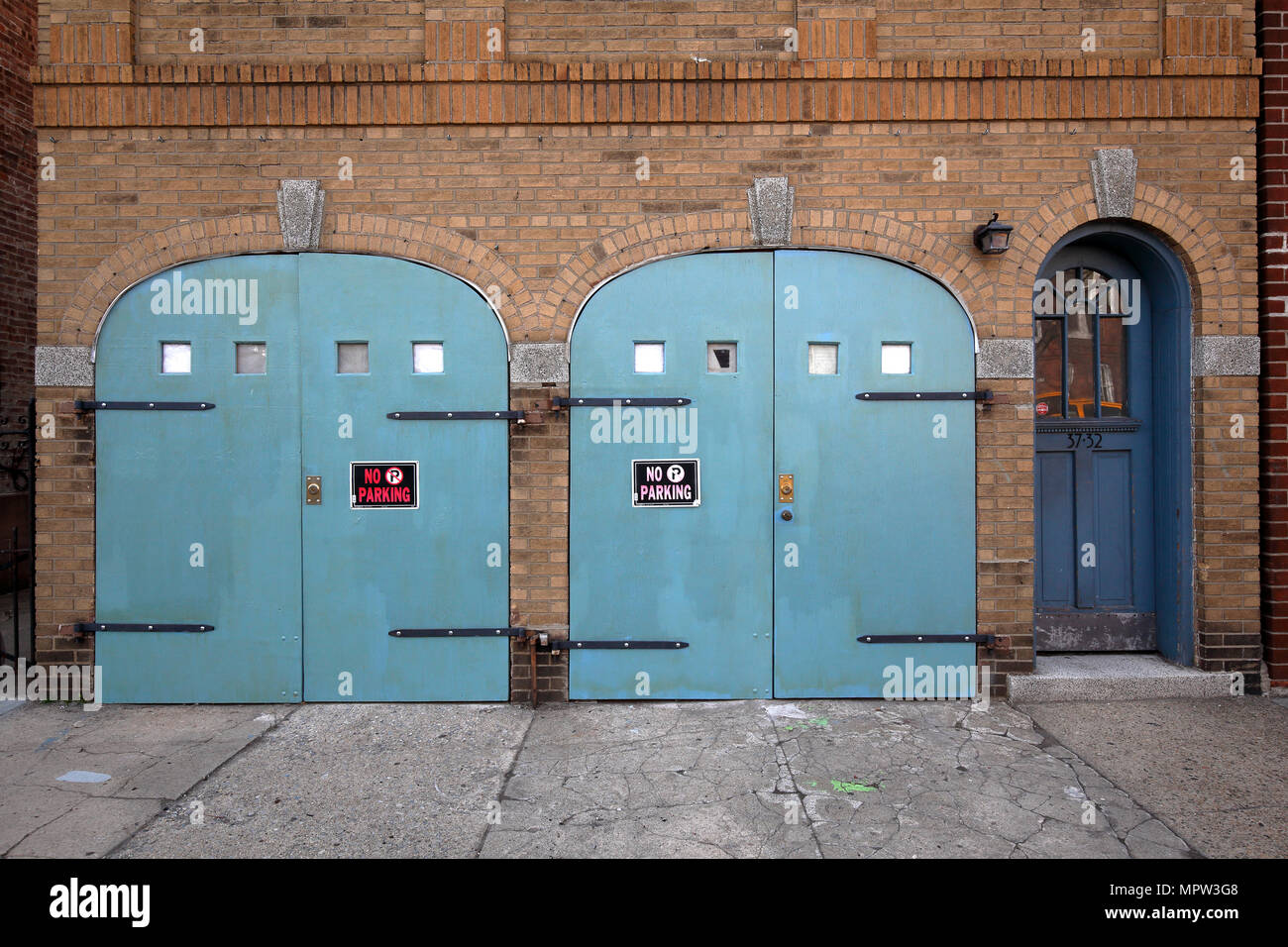 building with arched garage doors in Astoria, New York City - Stock Image
