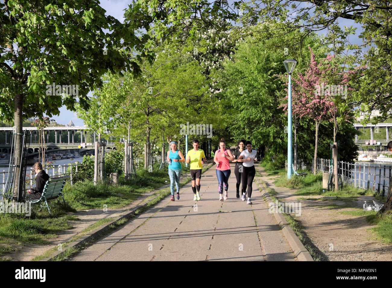 Young people jogging running along the Allées Des Cygnes near the Pont de Bir-Hakeim and River Seine in spring in Paris France Europe  KATHY DEWITT - Stock Image
