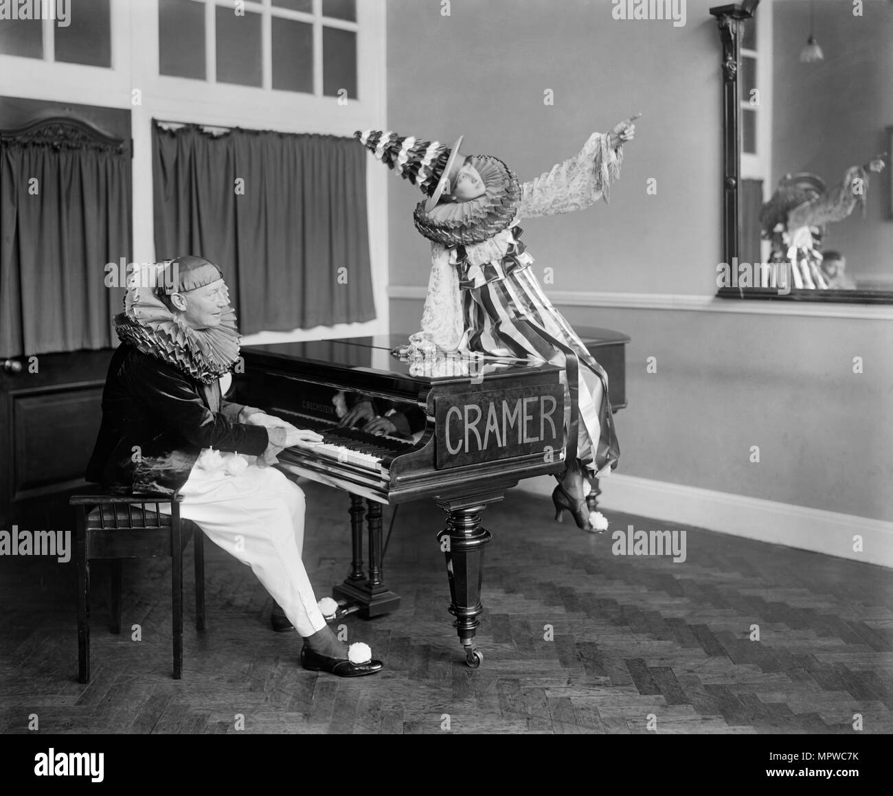 Two Pierrot clowns performing a routine with a piano, 1917. Artist: Bedford Lemere and Company. - Stock Image