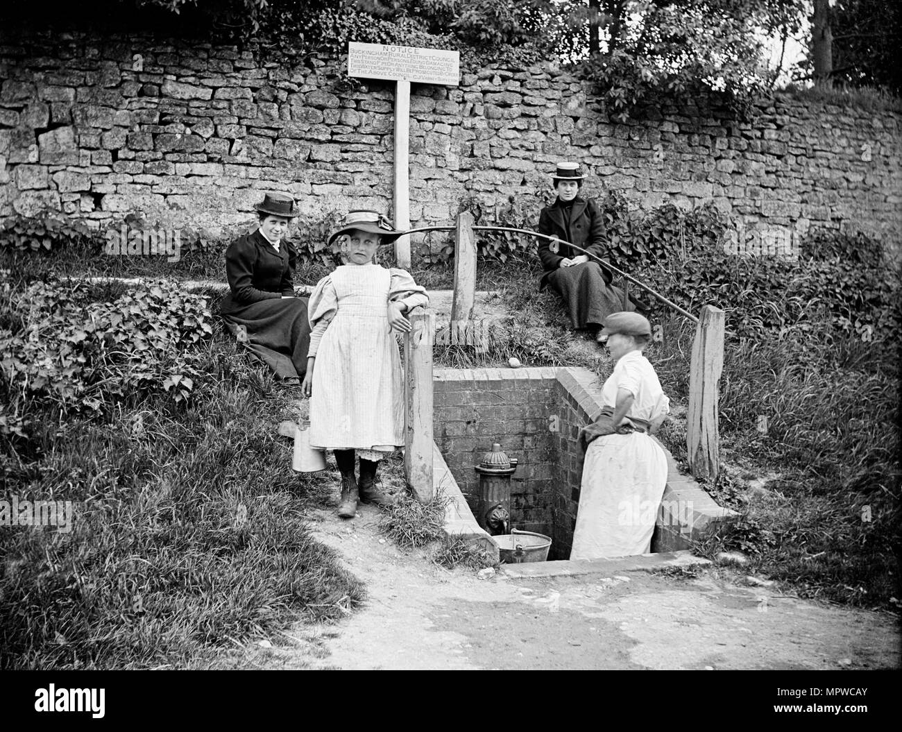 Collecting water from the village pump, Barton Hartshorn, Buckinghamshire, 1901. Artist: Alfred Newton & Sons. Stock Photo