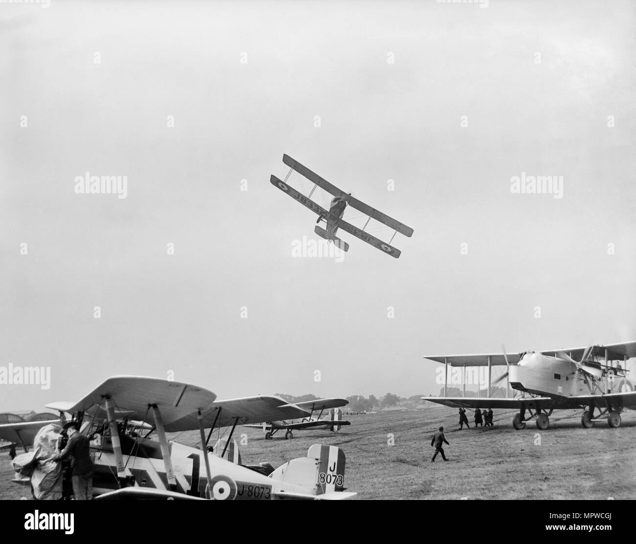 Avro 504 biplane flying very low over parked aircraft at the RAF Pageant, Hendon, London, 1927. Artist: Aerofilms. - Stock Image