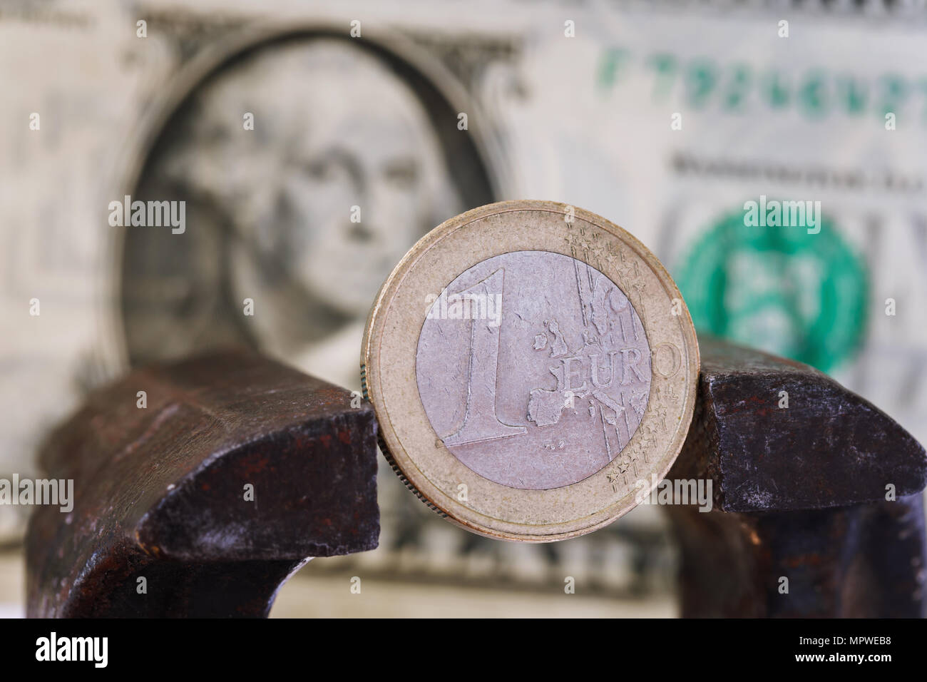 Financial dominance: one euro in a vice against the background of the American dollar with space for text - Stock Image
