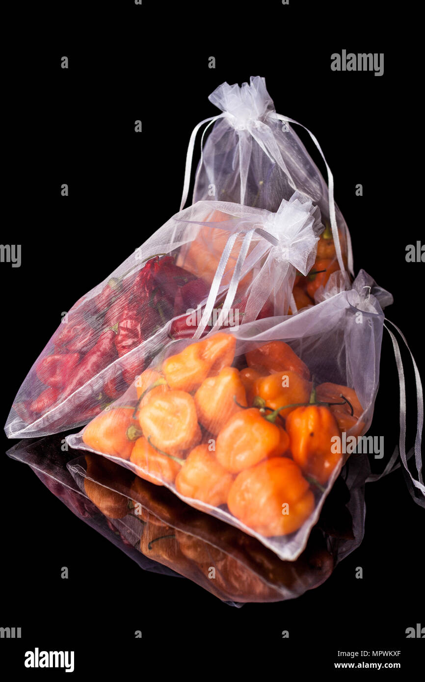 Three white gas transparent sacks with small yellow and red habanero peppers on black background with reflection - Stock Image