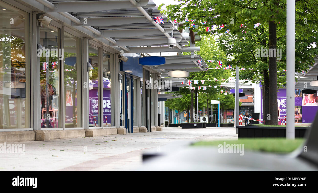 Empty and deserted shopping centre illustrating a decline in the high street caused by internet shopping in the UK - Stock Image