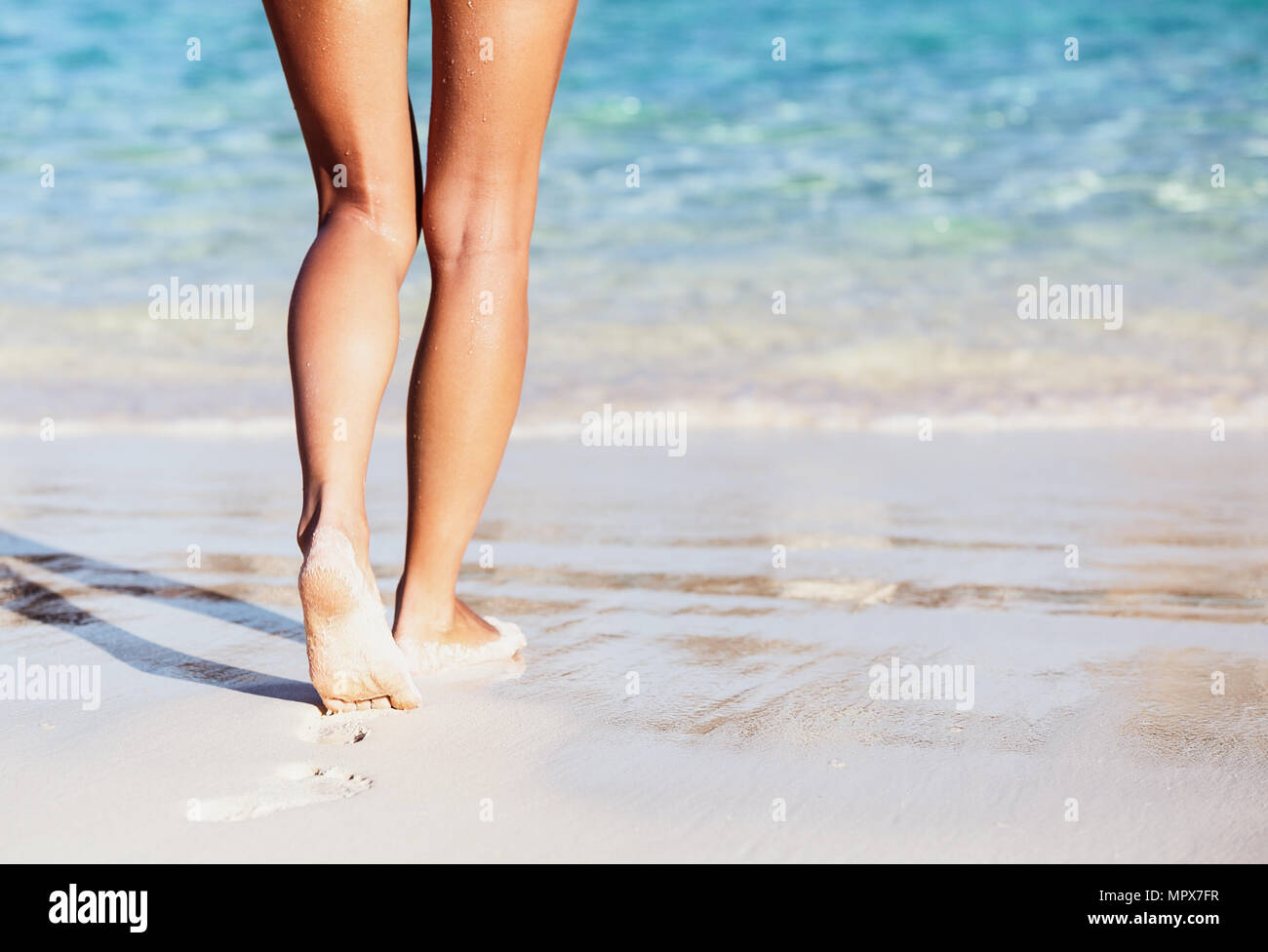 Woman walking into the sea, body part, perfect tanning women's legs, enjoying time on the beach, summer vacation concept - Stock Image