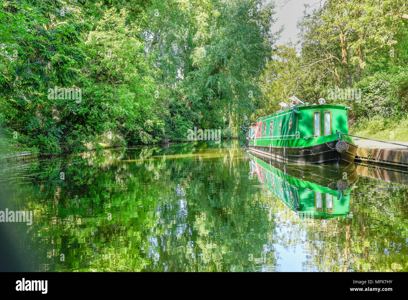 Narrowboat moored to the towpath on a sunny spring day at the Market Harborough arm of the Grand Union canal, England. - Stock Image