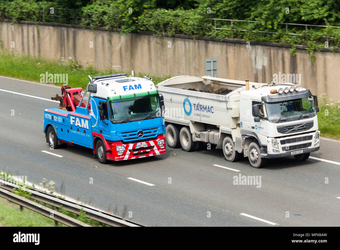 FAM commercial vehicle recovery breakdown truck passing a Tarmac branded Volvo FM410 tipper lorry on the M61 motorway near Farnworth. - Stock Image