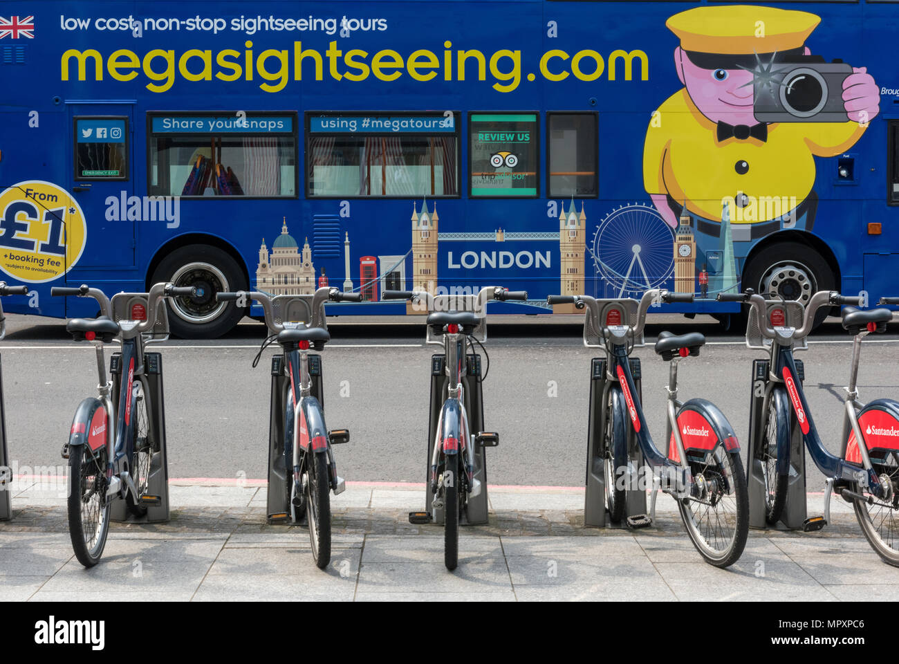 a sightseeing bus in the centre of london with borris bikes provided by TFL or transport for London in the foreground. Typically london tourism scene. - Stock Image