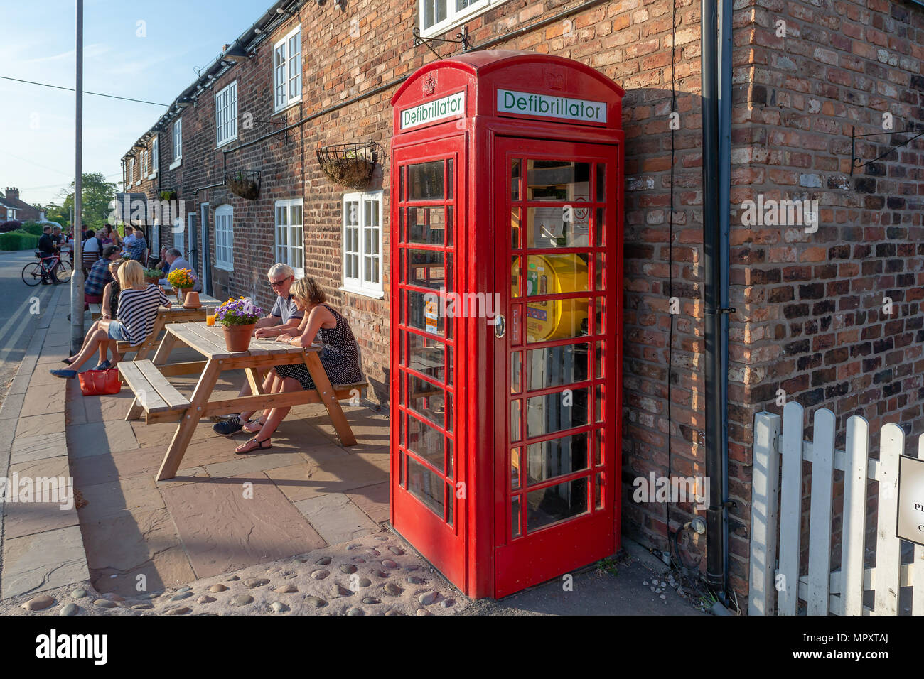Red K2 telephone box used as a library and defibrillator station outside The Hatton Arms public house in Hatton, Cheshire, England, UK Stock Photo