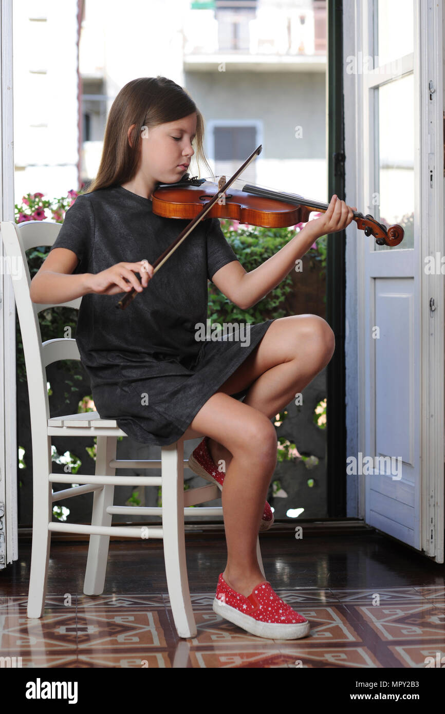 Girl playing violin while siting on chair at home - Stock Image