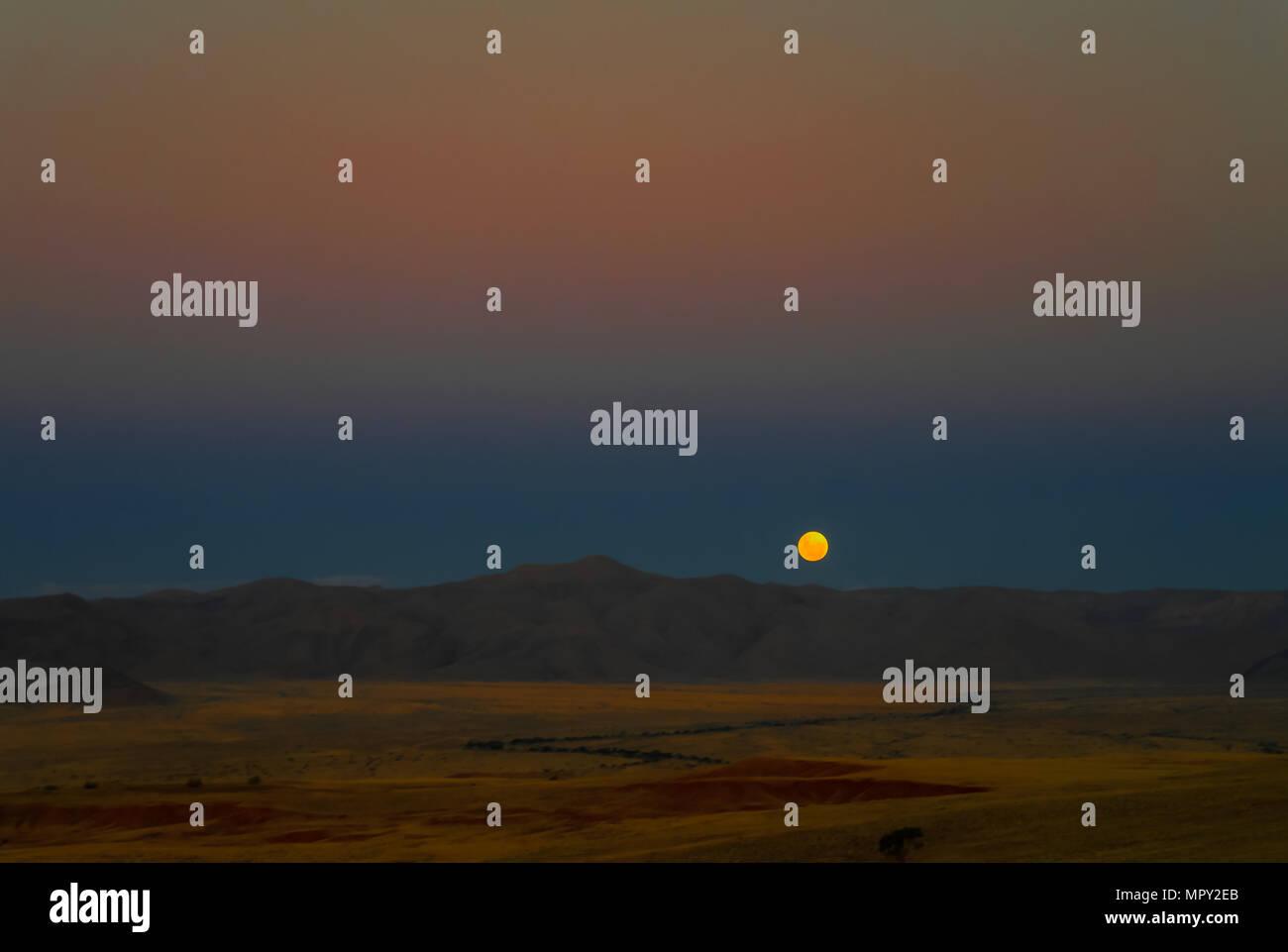 Full moon ascends over the dune in Namib desert, Namibia Stock Photo