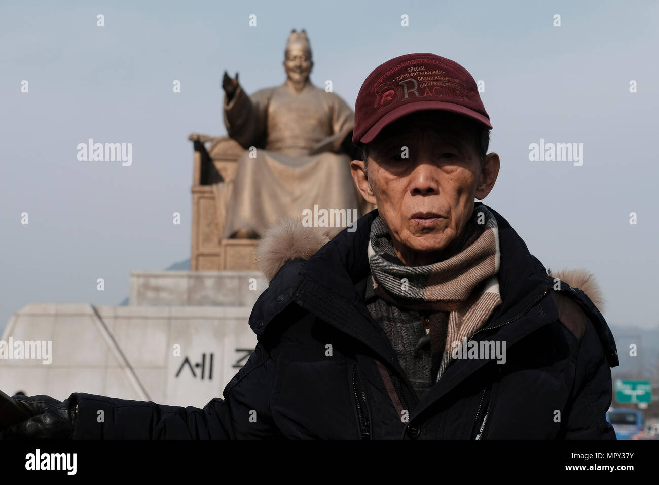 An elderly Korean man with the statue of Sejong the Great