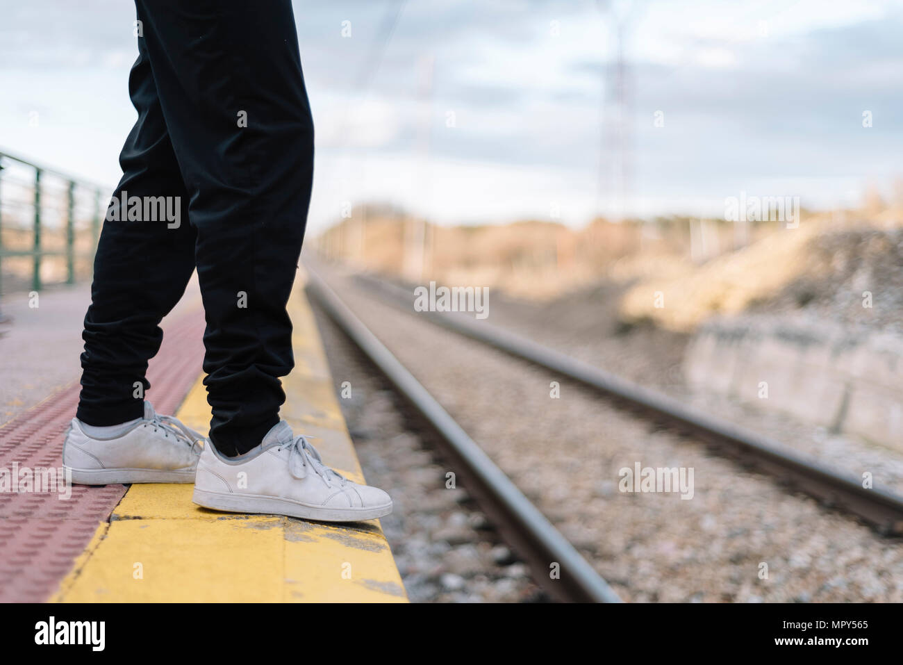 Low section of teenage girl standing at railroad station platform - Stock Image