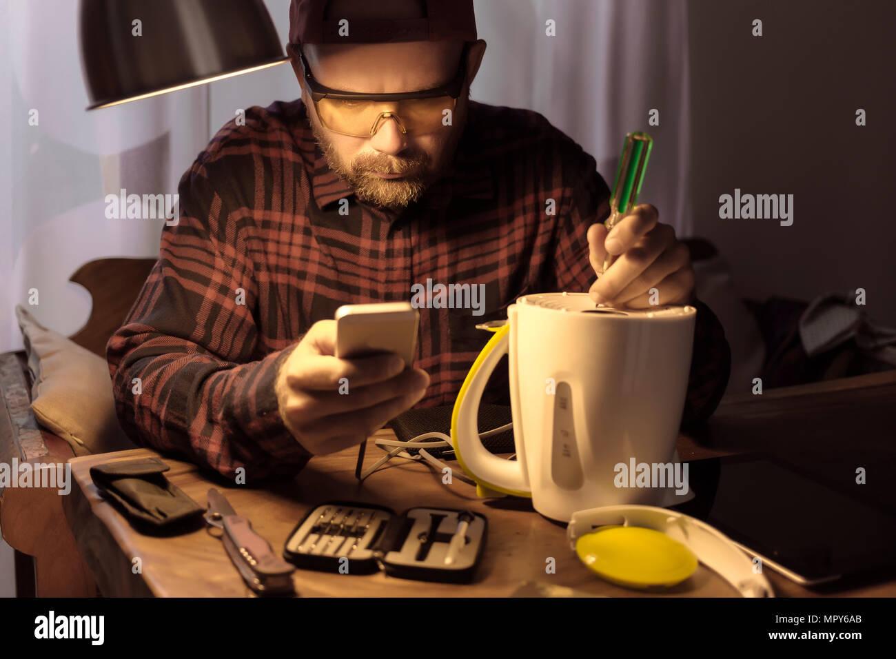 Man wearing protective eyewear while repairing appliance using smart phone at home - Stock Image