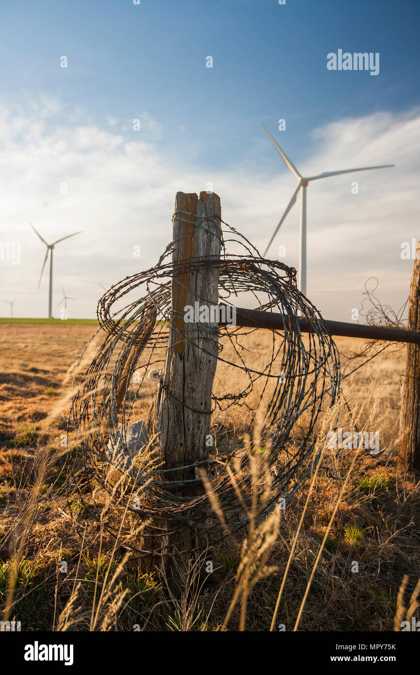 Barbed wire on wooden fence against windmills and cloudy sky at farm Stock Photo