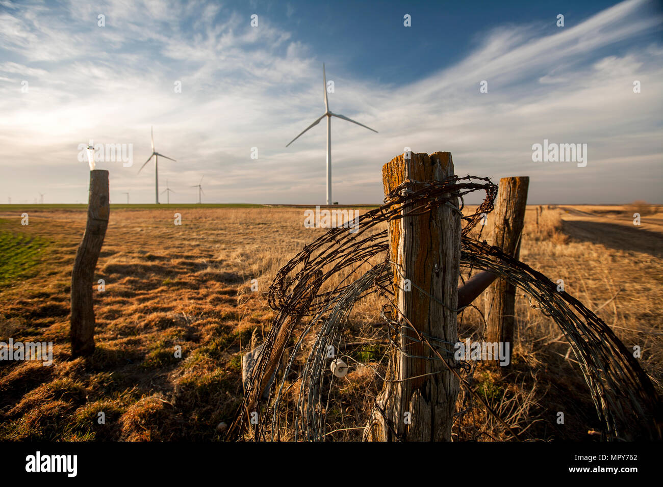 Barbed wire on wooden fence against wind turbines and cloudy sky Stock Photo