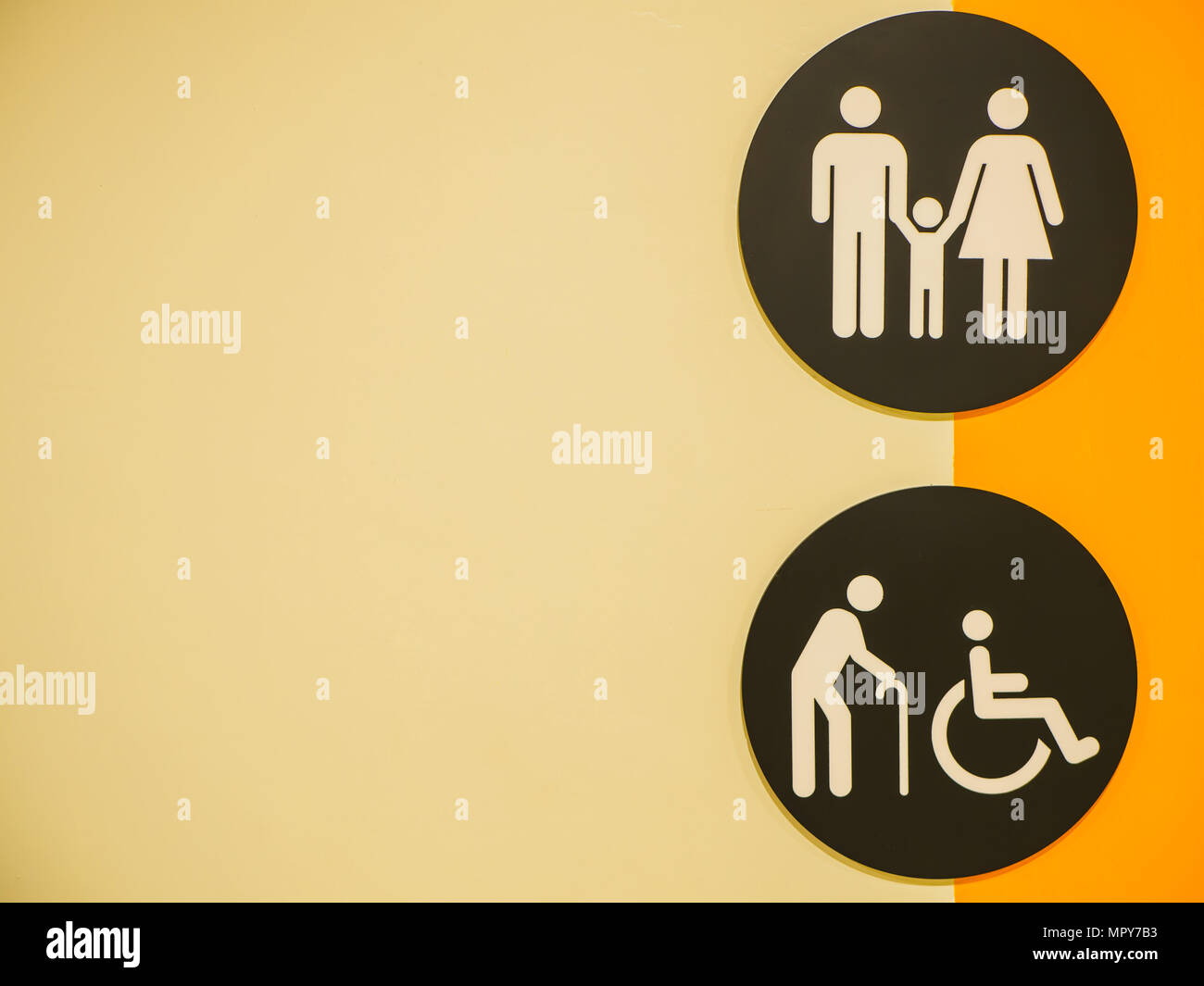 Public restroom signs with a disabled access symbol on the wall in shopping mall