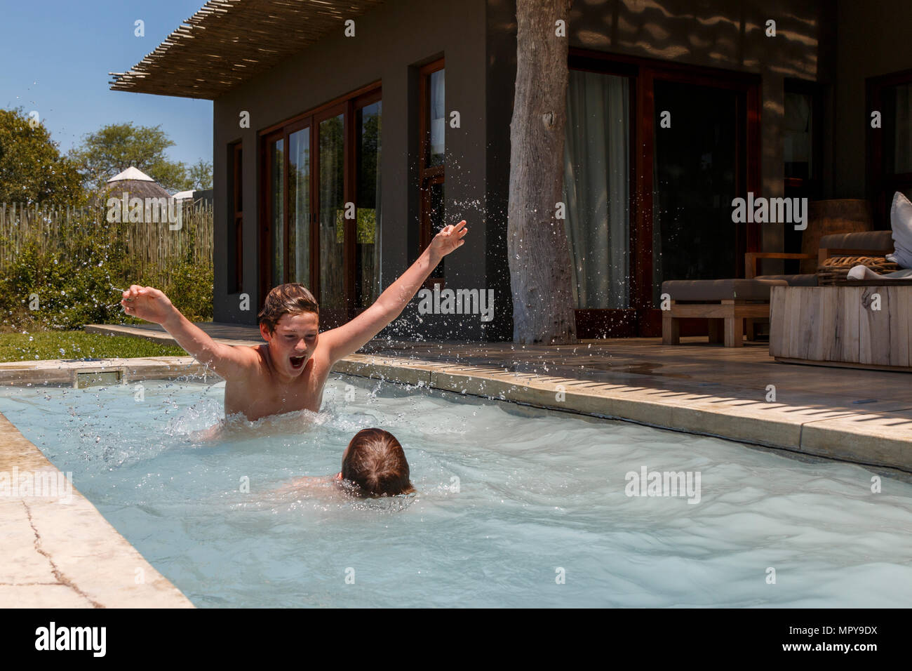 Playful brothers swimming in plunge pool against house during summer - Stock Image
