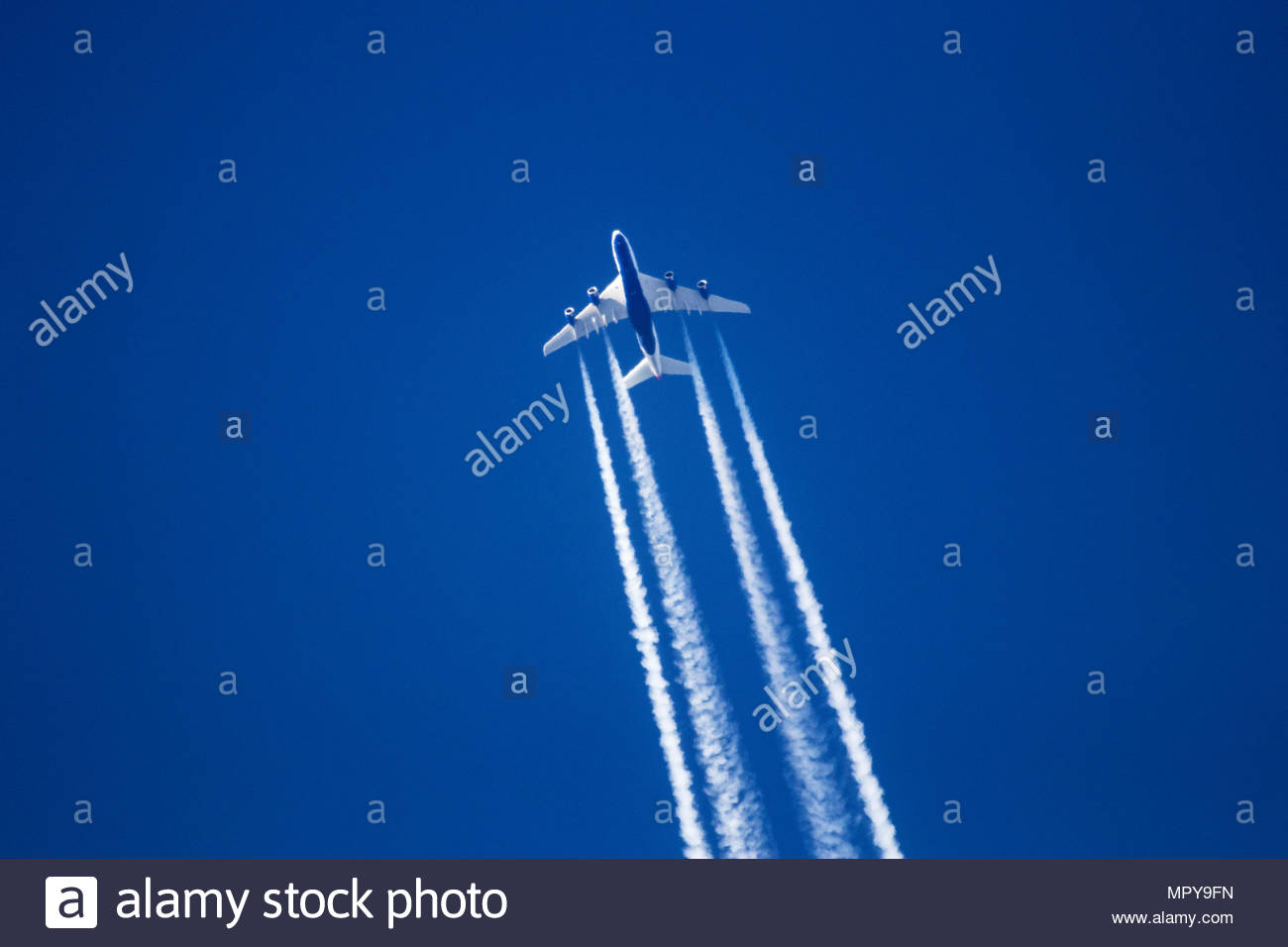 Low angle view of jet plane flying against clear blue sky - Stock Image