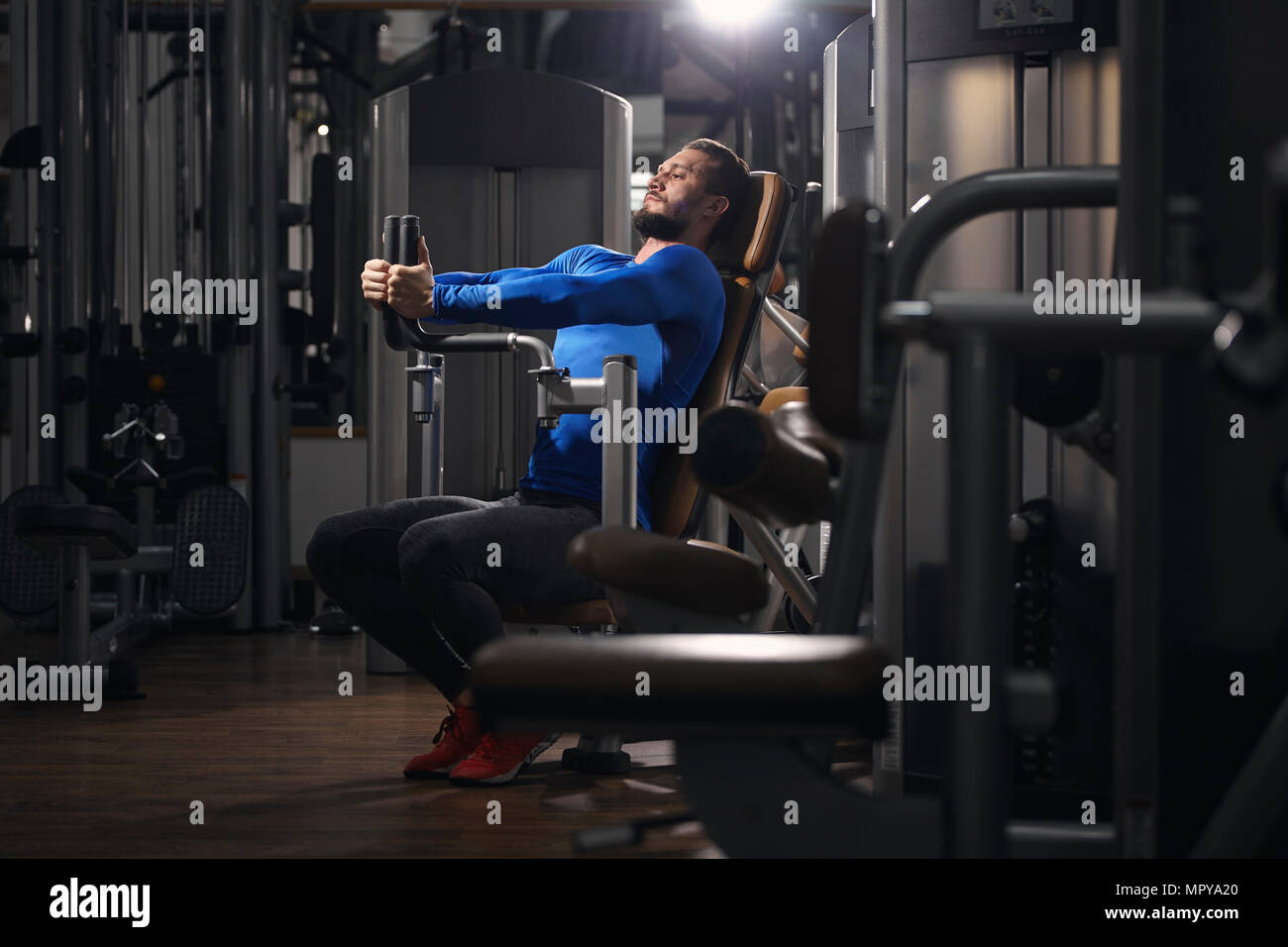 Man stretching on exercise machine at gym - Stock Image