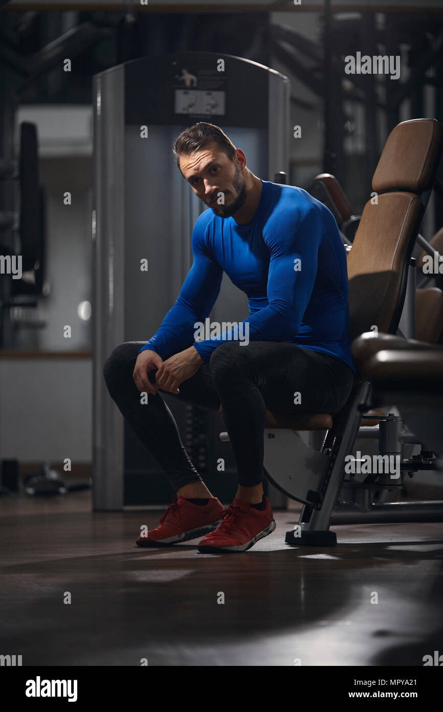 Portrait of confident man sitting on exercise machine at gym - Stock Image