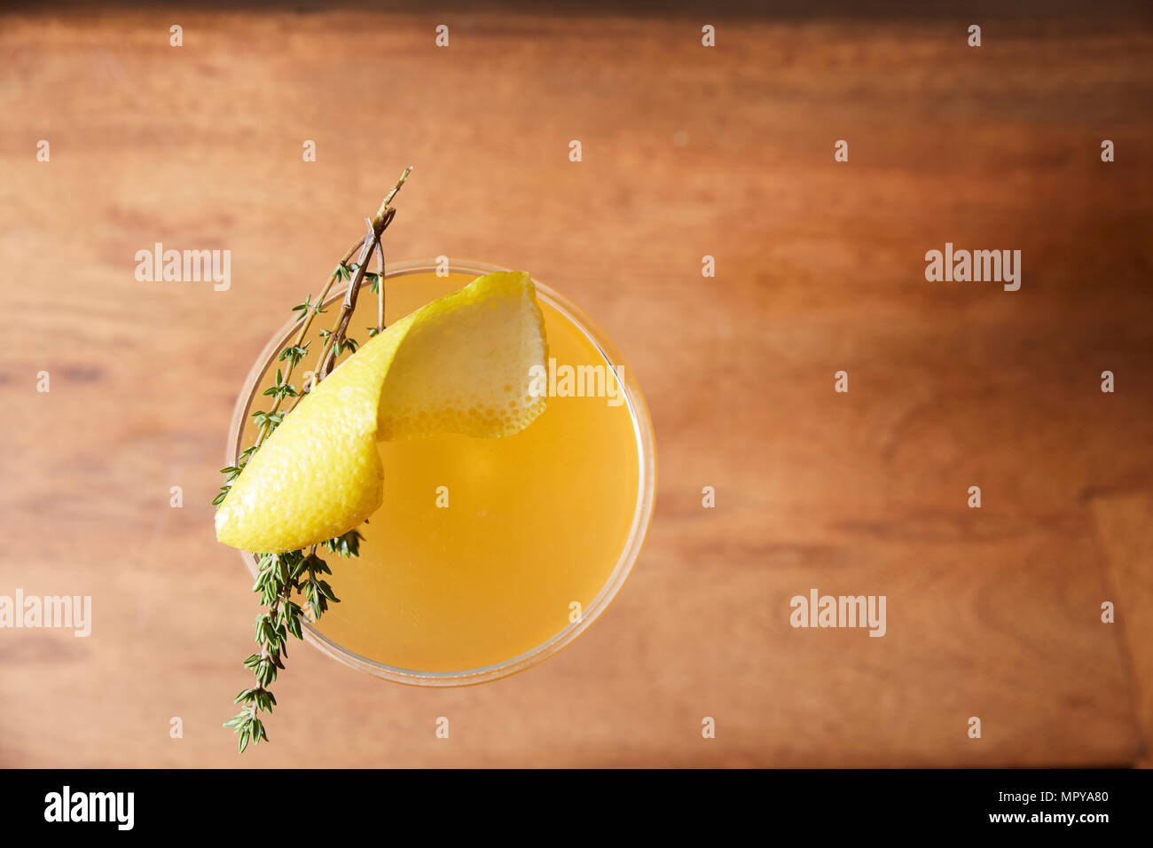 Overhead view of cocktail on wooden table - Stock Image