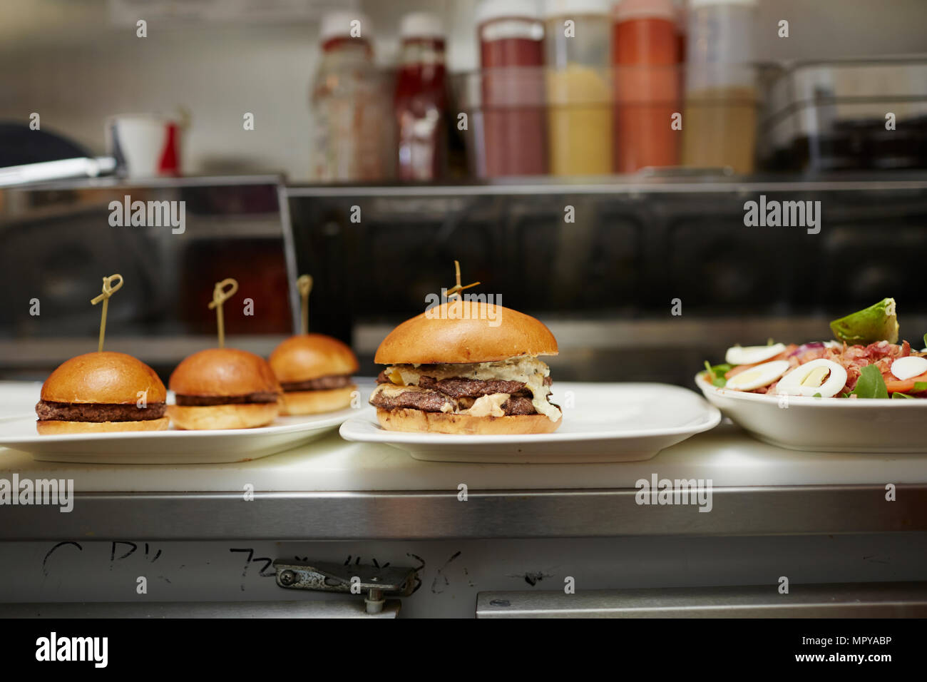 Burgers served in plates on kitchen counter - Stock Image