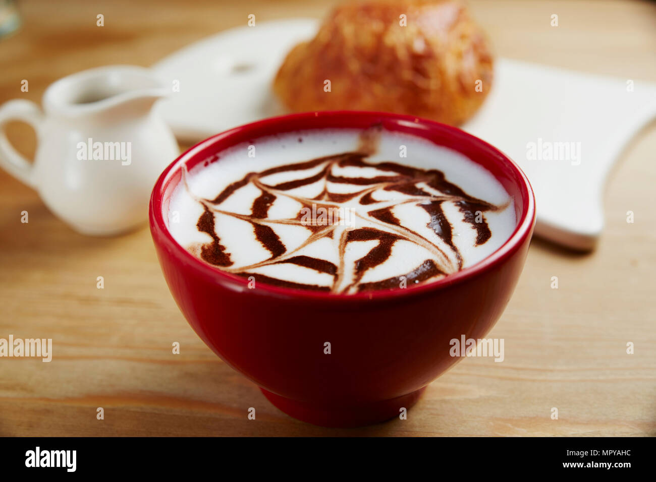 Close-up of frothy drink served in coffee cup on table at cafe - Stock Image